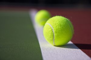 Two tennis balls on baseline of brand new tennis court